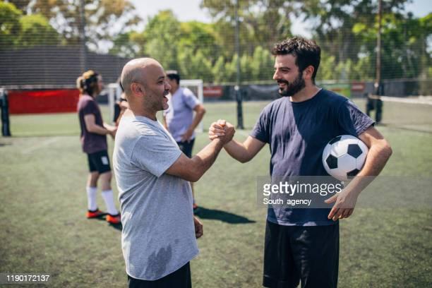 männliche fußballer handshake - fußball freundschaftsspiel stock-fotos und bilder