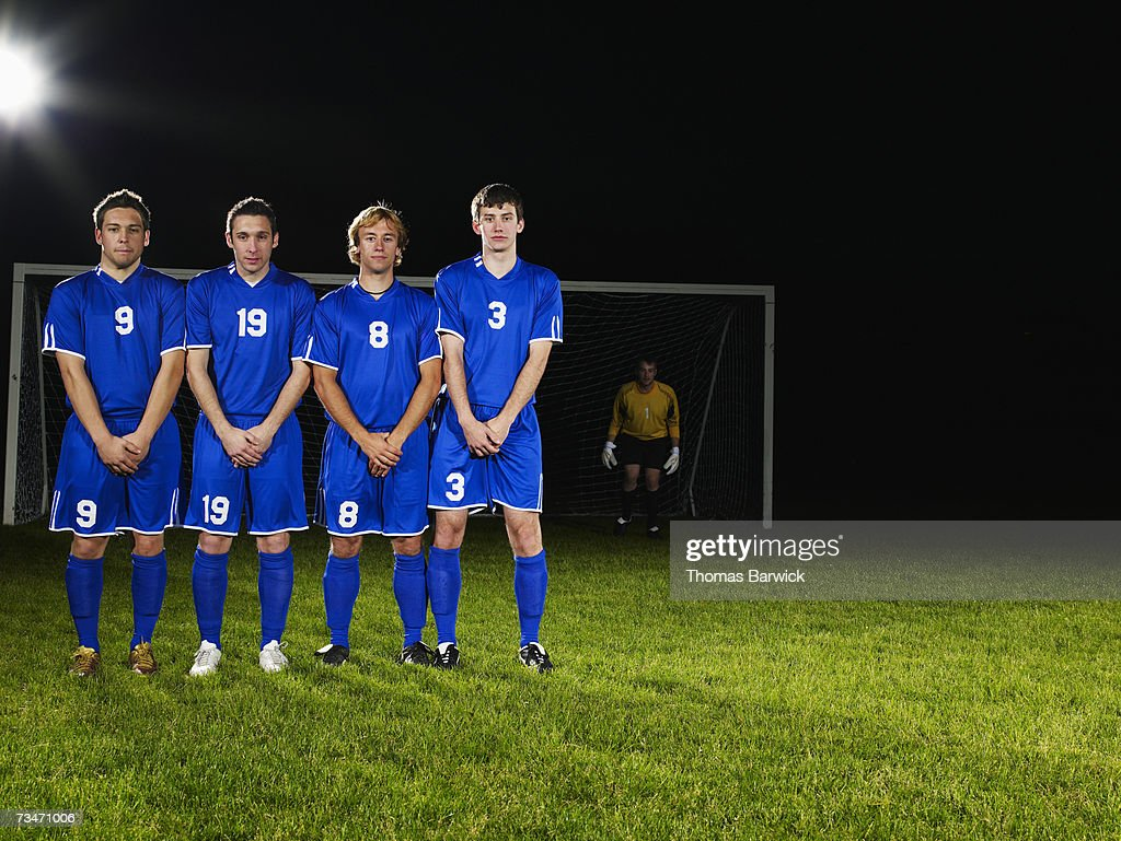 Male soccer players in defensive wall awaiting free kick : Stock Photo