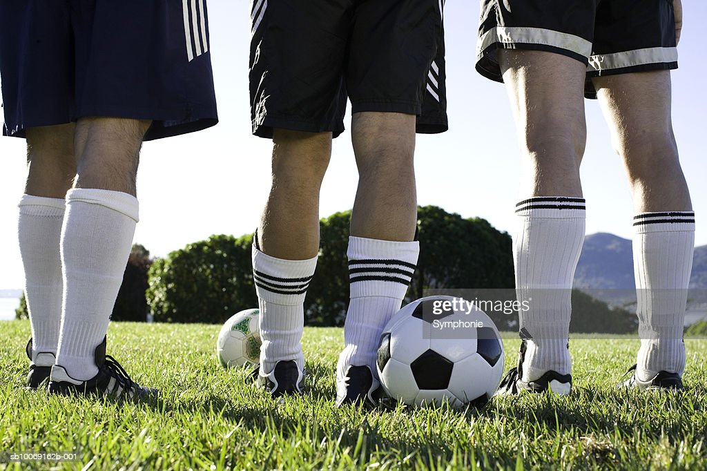 Male soccer players standing in field, low section, close-up : Stockfoto