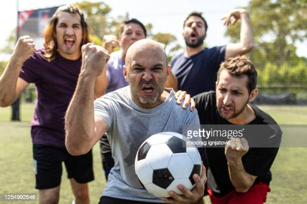male soccer team celebrating after winning competition on soccer field - exhibition match stock pictures, royalty-free photos & images