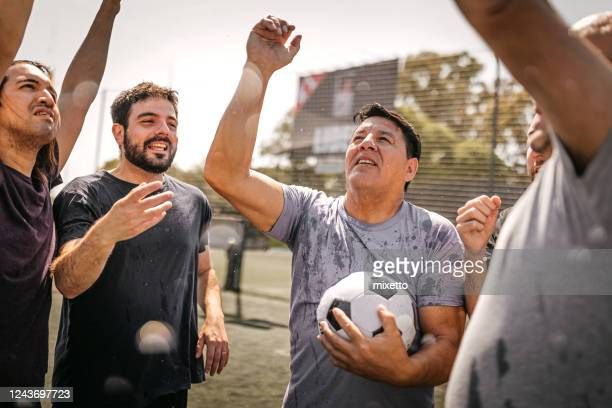 male soccer team celebrating victory - friendly match stock pictures, royalty-free photos & images