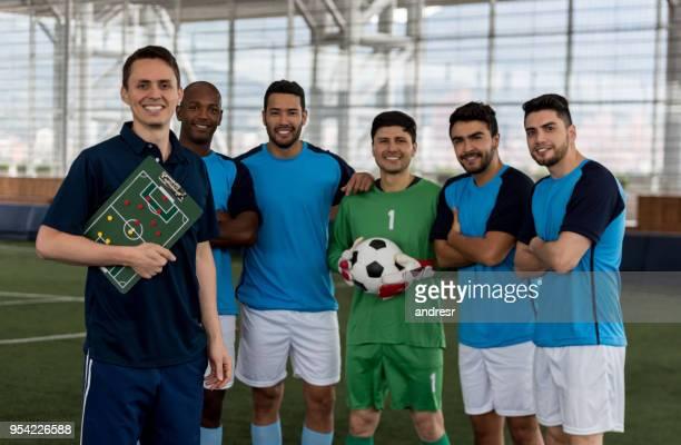 männlichen fußballmannschaft stehen hinter ihrem trainer alle blick auf die kamera zu lächeln - fußballmannschaft stock-fotos und bilder