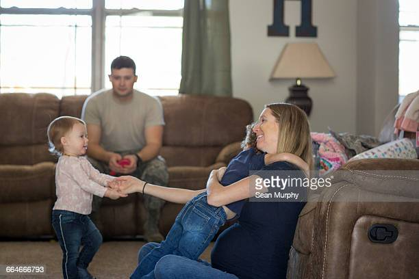Male soldier and wife playing with daughters in living room at air force military base