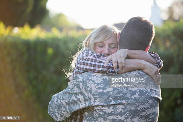 male soldier hugging mother on street at homecoming - wiedersehenstreffen stock-fotos und bilder