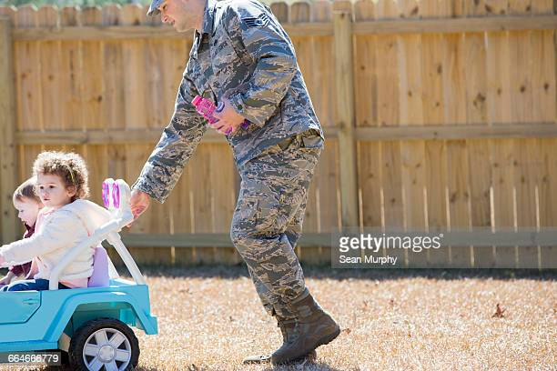 Male soldier pushing daughters in toy car at air force military base