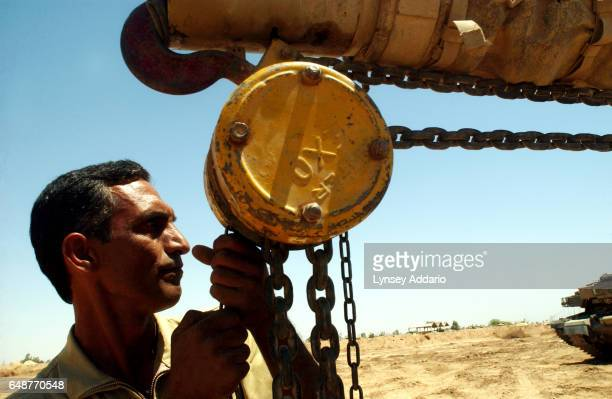 A male soldier with the Mujahedeen Khalq Organization MKO realigns a tank barrel on their main base at Camp Ashraf near Baghdad May 12 2003 The MKO...