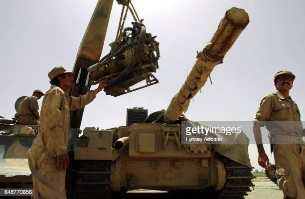 Male soldiers with the Mujahedeen Khalq Organization MKO remove an engine from one of their tanks near Baghdad Iraq May 18 2003 The MKO an Iranian...