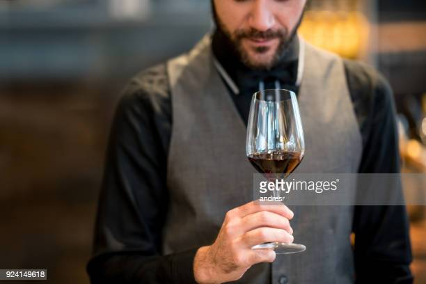 Male sommelier at a winery tasting and smelling a wine served in a wineglass