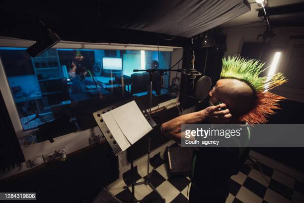 male sound engineer listening male punker singer singing into microphone in recording studio - punk music stock pictures, royalty-free photos & images