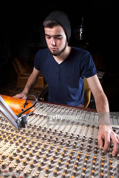 Male sound engineer using a studio mixing desk