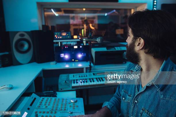 male sound engineer working while male punker singer singing into microphone in recording studio - punk music stock pictures, royalty-free photos & images