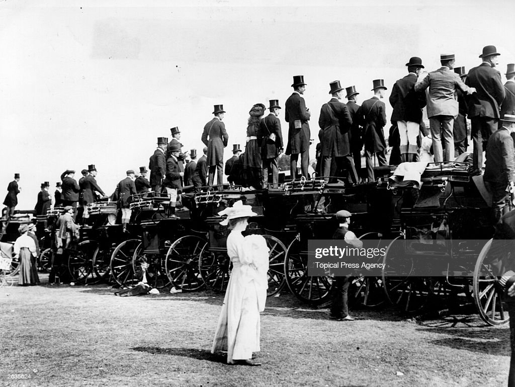 Male spectators watch the races from their carriages while a woman is left behind.