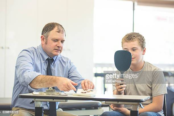 Male speech therapist helping a teenage patient inside of a clinic