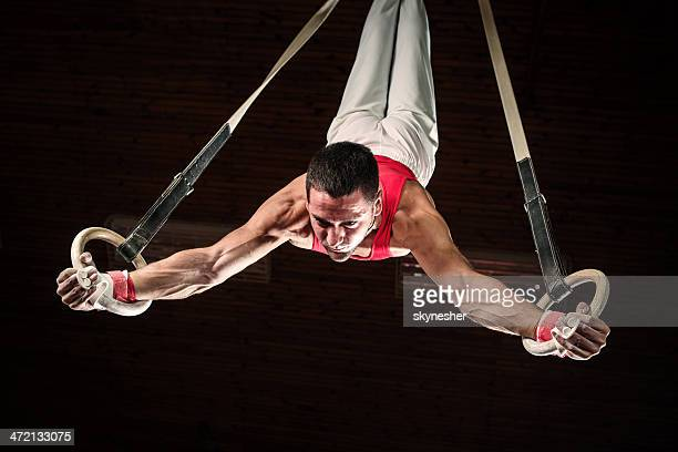 male sportsman on gymnastics rings. - gymnastics stock pictures, royalty-free photos & images