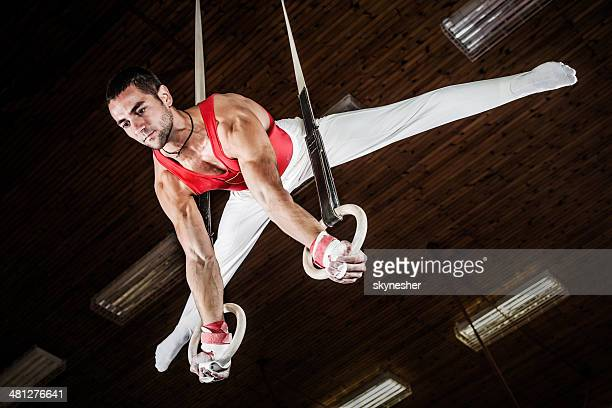 Male sportsman on gymnastics rings.