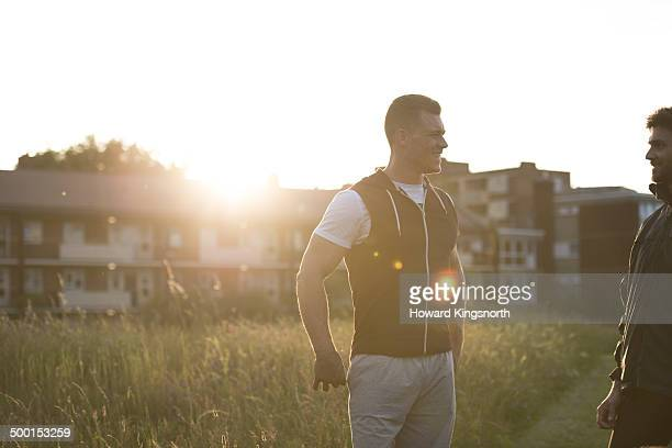 2 male sportsmen talking at sunset - center athlete stock pictures, royalty-free photos & images