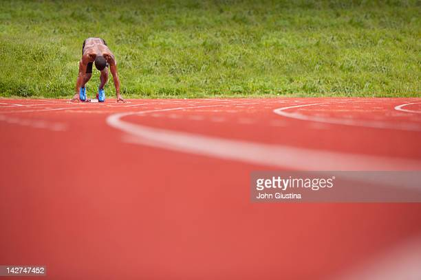 Male sprinter in blocks, awaiting starting gun