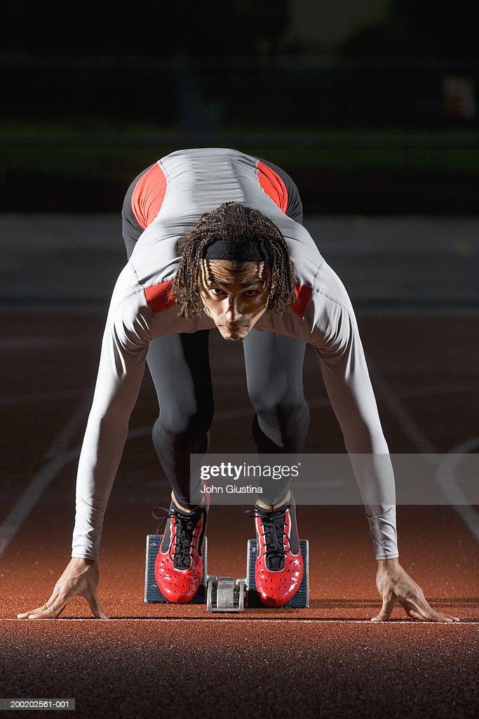 Male sprinter in blocks, in ready position : Bildbanksbilder