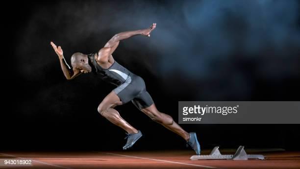 male sprinter leaving starting blocks - sprint imagens e fotografias de stock