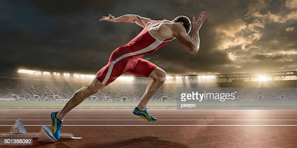 male sprinter sprint starts from blocks in athletics stadium - athletics stock photos and pictures