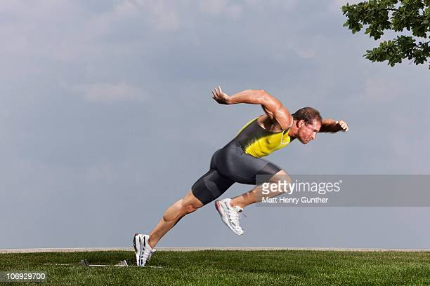 male sprinter taking off from starting blocks - スプリント競技 ストックフォトと画像