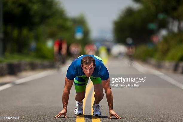 Male sprinter taking off on urban running path