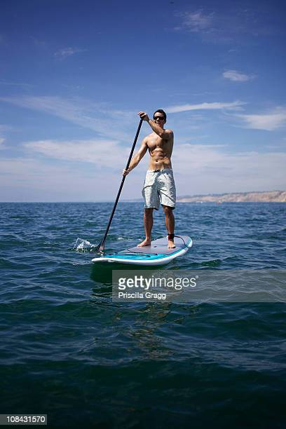 Male stand up paddling in the ocean.