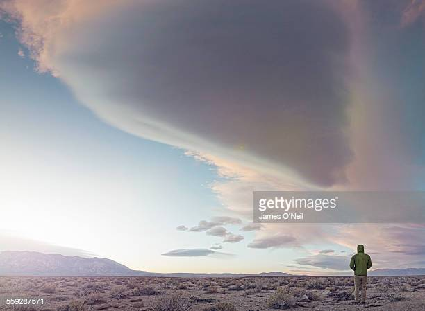male standing under dramatic clouds
