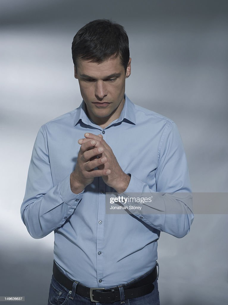 Male standing with hands together looking down : Stock Photo