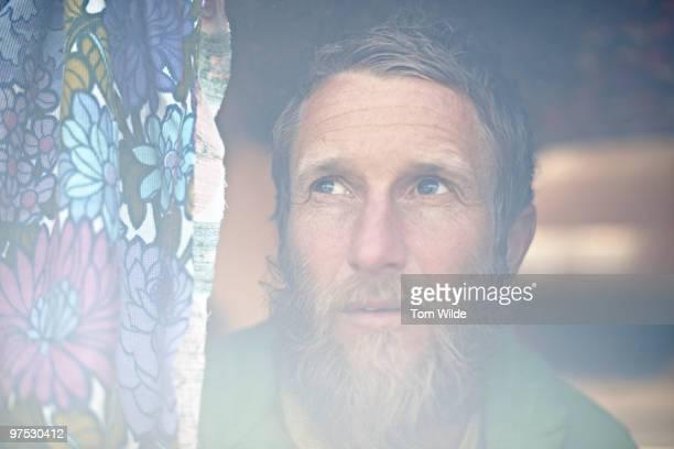 male staring through window with floral curtain - starren stock-fotos und bilder