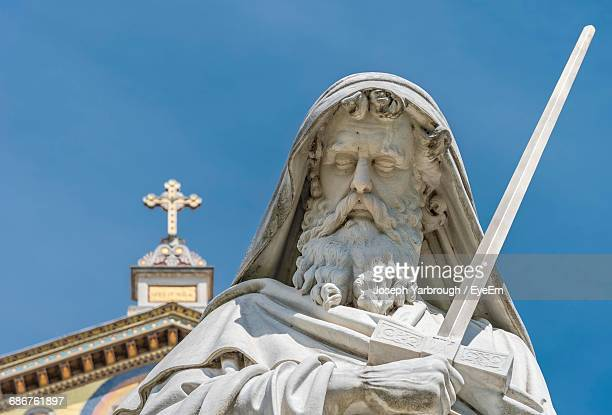 male statue against basilica of saint paul outside the walls - paul the apostle stock pictures, royalty-free photos & images