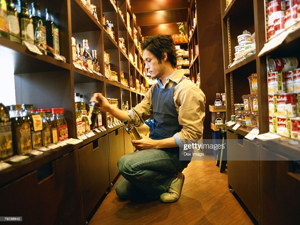 Male store attendant replenishing grocery : Stock Photo
