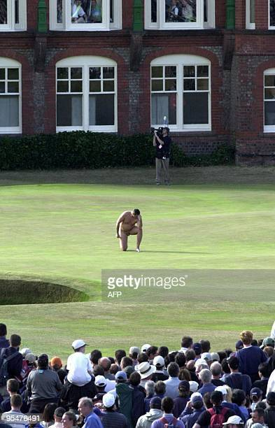 A male streaker strikes a pose on the 18th green in front of the clubhouse 22 July 2001 just seconds after David Duval won the Open Golf Championship...
