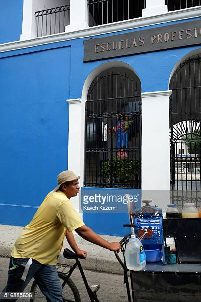 CARTAGENA of INDIAS COLOMBIA JANUARY 29 2016 A male street vendor pushes his cart pass a school where a statuete of the Virgin Mary with newly born...