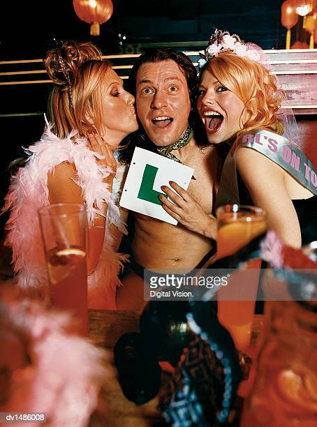 male stripper being kissed by two women at a hen night in a nightclub - jock strap stock photos and pictures