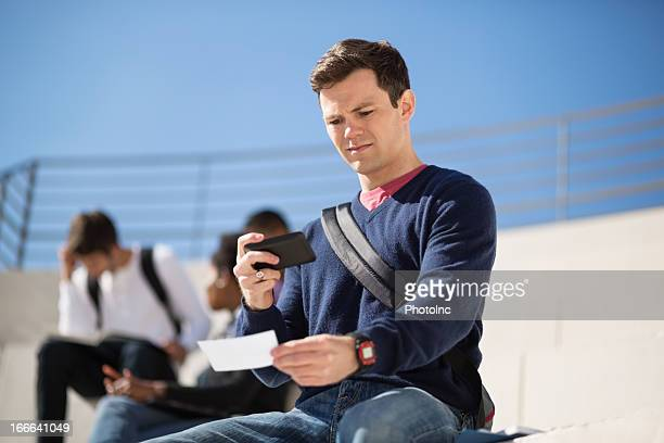 Male Student Depositing Check Through Phone