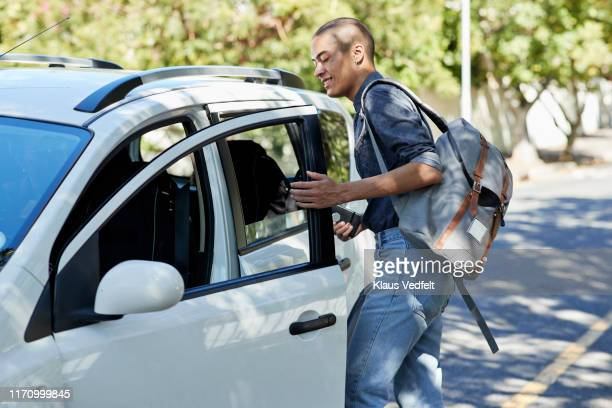 male student entering car on roadside - entrar imagens e fotografias de stock