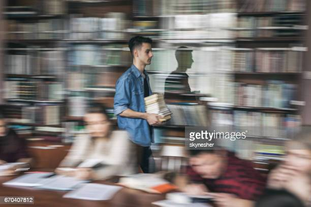 Male student in blurred motion carrying stack of books in library.