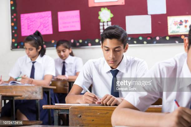 male student in classroom writing in notebook - stock image - india stock pictures, royalty-free photos & images