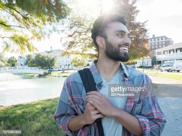 un varón, estudiante en la universidad camina con su mochila - india summer fotografías e imágenes de stock