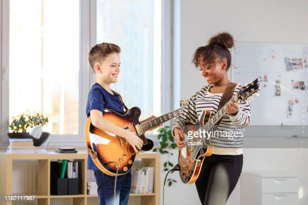 male student learning guitar from trainer - musical instrument stock pictures, royalty-free photos & images