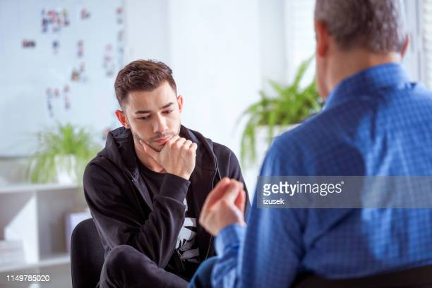male student listening to therapist in session - sadness stock pictures, royalty-free photos & images