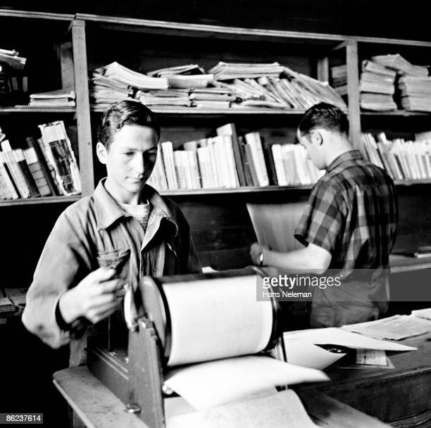 Male student operates a small hand-powered duplication machine while a man in the background looks a printouts, Traiguen, Araucanía Region, Chile,...