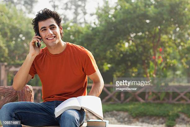 Male student reading book and talking on mobile phone