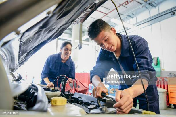 Male student repairing car, woman watching