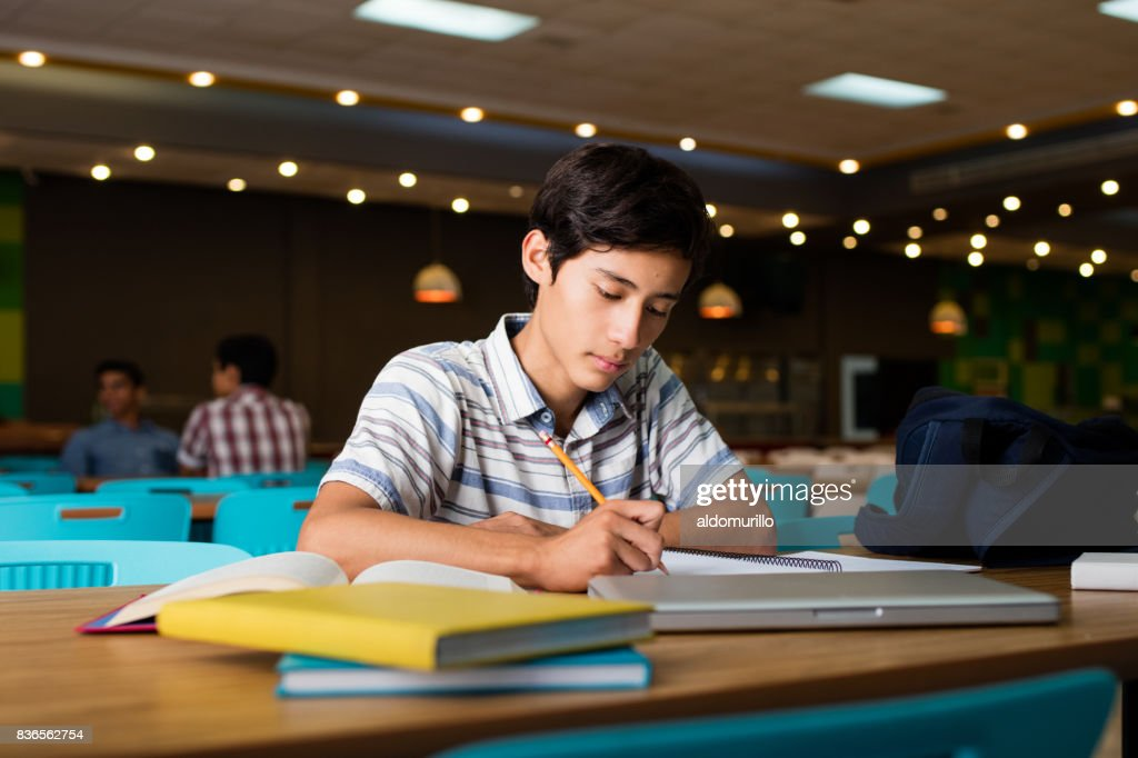 Male student sitting and writing : Stock Photo