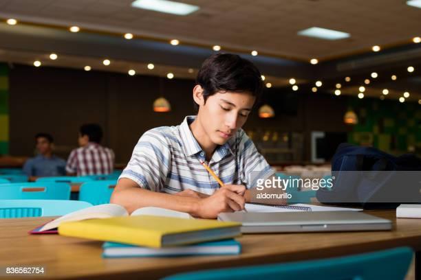 Manlig student sitta och skriva