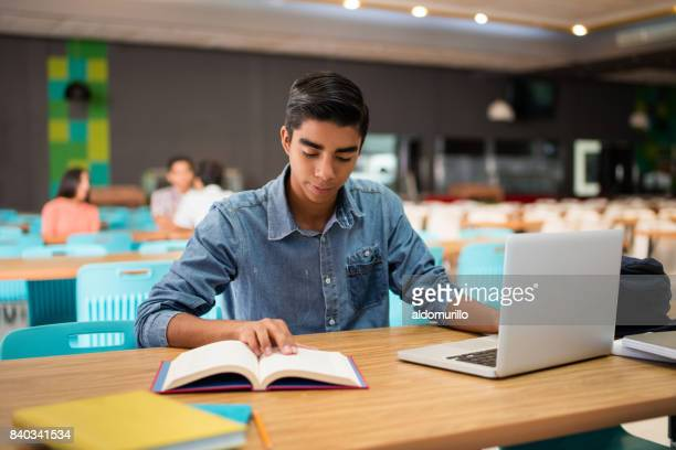 Male student sitting with laptop and book