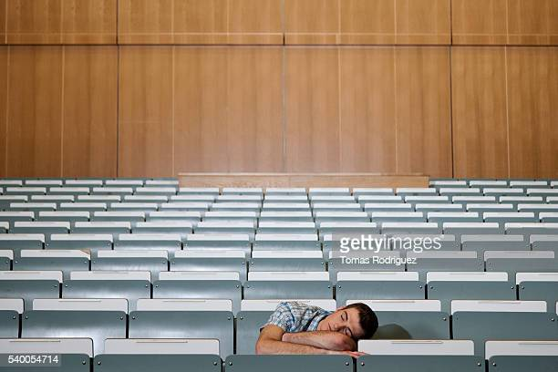Male student sleeping in lecture hall