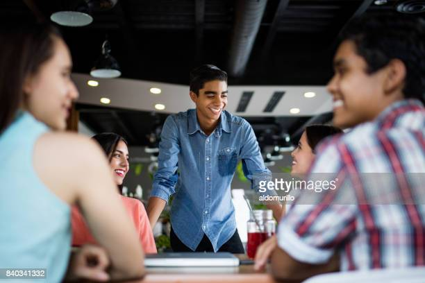 Male student standing and smiling at students sitting at table